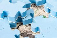 US dollar hidden under puzzle