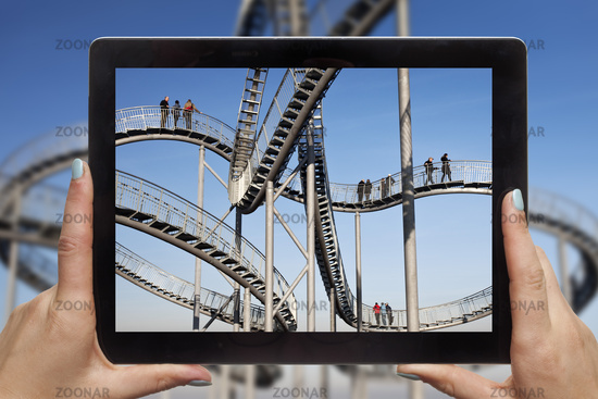 holding a tablet PC in the hands with a photo of Tiger and Turtle in front of the real object
