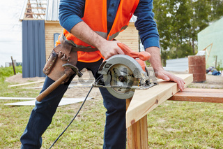 Handwerker sägt Holzbalken