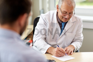 doctor writing prescription for patient at clinic