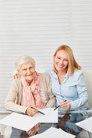 Frau hilft Seniorin beim Ausfüllen von Formularen