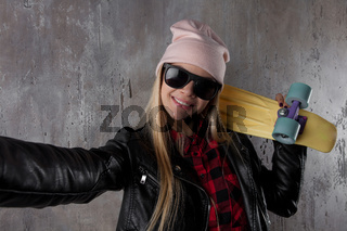 Blond teenager girl in black sunglasses and pink hat with yellow skateboard make selfie. In front of concrete wall.