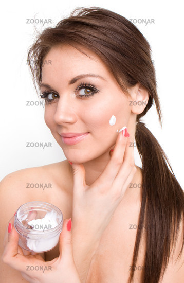 brunette girl with a bit of cream on her beauty face