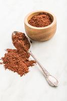 Dark cocoa powder in spoon.