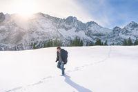 Man walking through snow in mountains