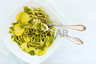 Closeup of linguine pasta with pesto genovese and potatoes over a table