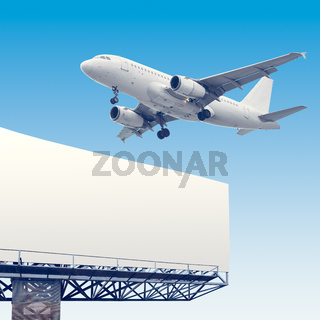 Airliner flying over billboard