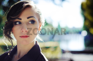 Close up face portrait of smart girl with old-fashioned hairstyle outdoor in brown coat.