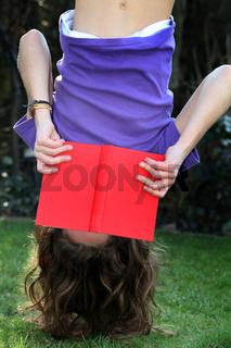 Ein Kind liest ein Buch - kopfüber