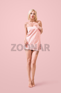 Beautiful young woman wrapped in bathing towel