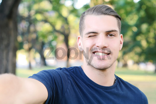 Young latin man taking a selfie in a park.