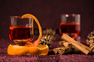 Closeup of alcoholic punch drink with orange peel and cinnamon sticks