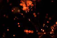 Abstract celebration festive lights using a defocused bokeh effect with a black background. The sparkling orange colored lighting is created from the blur of intense Christmas decorations.