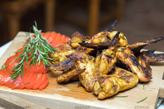 Pile of roasted grilled chicken wings on oak wooden board.