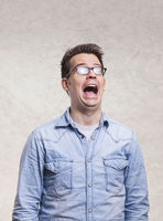 Portrait of a shocked, screaming, stunned or surprised young man -  isolated on light gray wall back