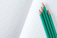 Squared exercise book and four pencils