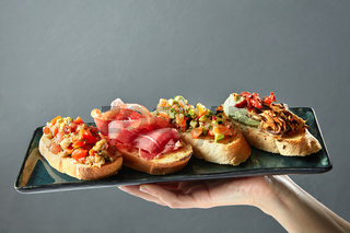 delicious variety of Italian bruschetta on a ceramic tray