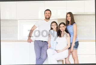 Adorable young big family embracing on kitchen