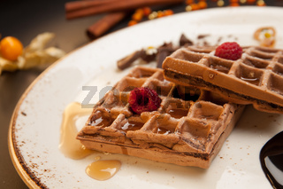 Plate of belgian waffles with caramel sauce and fresh berries