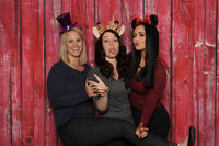 3 naughty girls in front of a photo box with red background