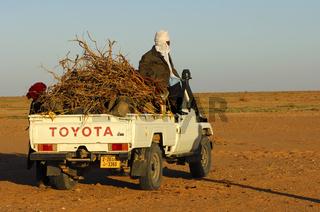 Beduine sitzt auf einen Jeep mit Feuerholz in der Sahara