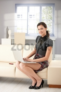 Pretty girl using laptop at home smiling