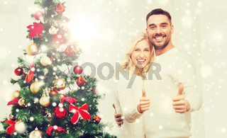 happy couple showing thumbs up with christmas tree