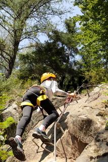 Junges Mädchen klettert Naturfelswand