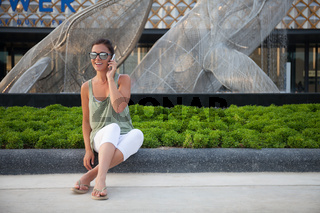 Young girl talks on the smartphone, she is wearing white trousers, green t-shirt and sunglasses