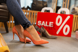 young woman trying high heeled shoes at store