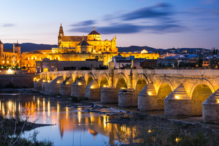 Illuminated Roman Bridge and Mosque-Cathedral at twilight in Cordoba, Spain