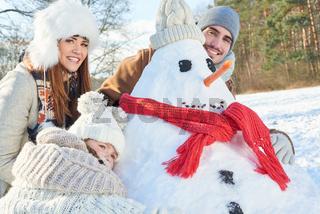 Familie spielt im Garten mit Schneemann