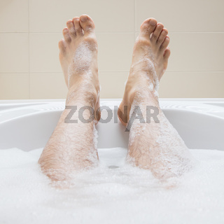 Men's feet in a bathtub, selective focus on toes