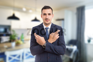 Real estate agent with fingers crossed on indoors background