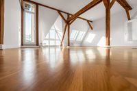 empty  room with wooden floor and roof beams - penthouse