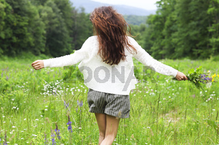 Happy pretty brunette woman in chamomile field