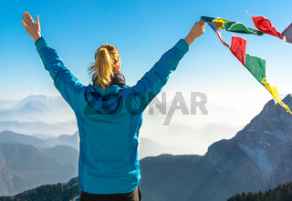 Happy success winning woman on summit arms up holding flag.