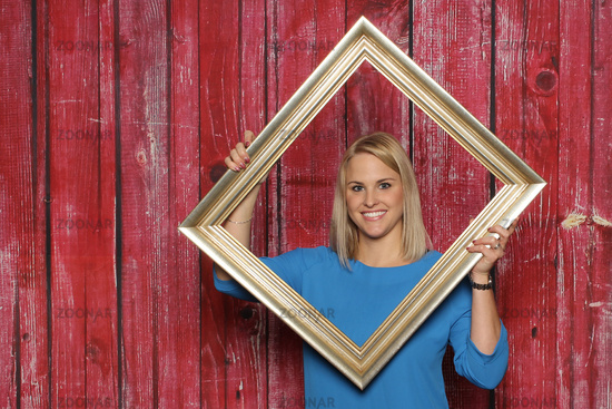 blonde girl looking through a picture frame and smiling