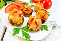 Champignons stuffed with meat and peppers in plate on board