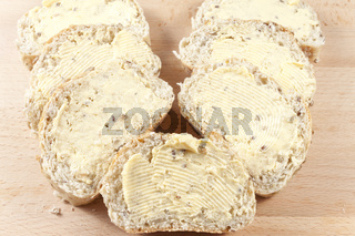 Seven buttered slices of sunflower seeded bread