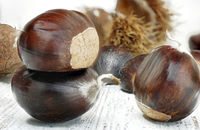Close with a few fresh cooked chestnuts on a wooden table.