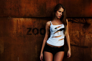 The beautiful girl model costs at a rusty wall