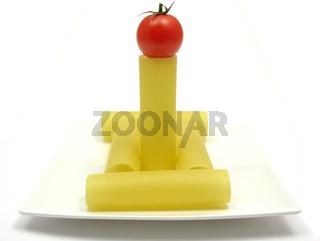 Mehrere ungekochte Cannelloni auf einem Teller mit Tomate arrangiert