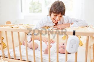Mutter streichelt Säugling im Babybett
