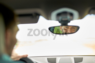 rearview mirror reflection of man driving car