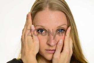 Junge blonde Frau stützt Ihren Kopf in die Hände