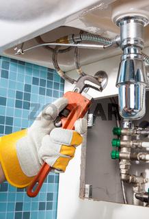 Repairing a pipe under sink. Plumber