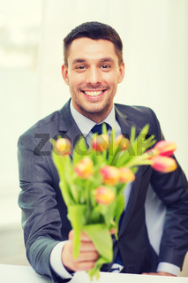 smiling handsome man giving bouquet of flowers