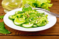 Salad from spinach and cucumber with fork on board