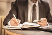 Senior business man writing down calculations